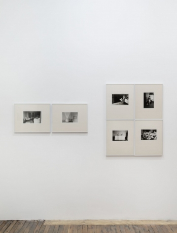 A photograph that is a tighter crop of the back wall of the gallery. There are 2 photographs next to one another in a row, landscape-oriented. There are 4 photographs at the right that are arranged in a rectangle with all corners touching. The images are installed in cream mattes with silver frames.