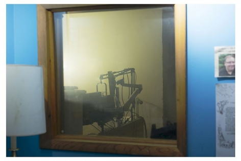 A photograph of an interior scene. The central focus is a mirror framed in wood with an audio setup reflected. At the left is a cropped lamp; at right is an excerpted and illegible newspaper article and written piece of paper. The wall upon which the mirror is hung is blue.