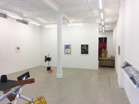 a photograph of the gallery with sculptures on the ground and several works hung on the wall
