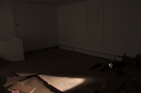 A photograph of the gallery floor. There is nothing on the wall, and panels of cardboard spread throughout the floor. They are used, the room is mostly dark