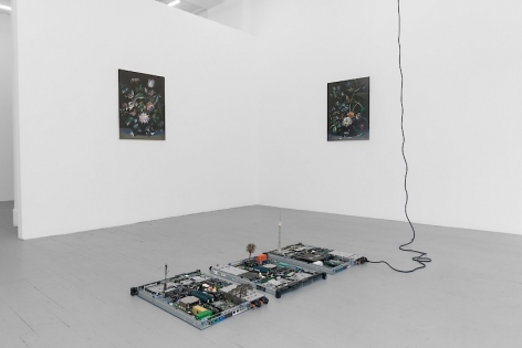 A photograph of 2 paintings on a wall, mirroring one another on 2 walls around the corner. There is a circuit board sculpture on the ground.
