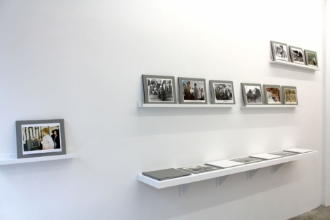 A photograph of color and black and white photographs, framed in gray paper, on several shelves, propped against the wall or laying flat