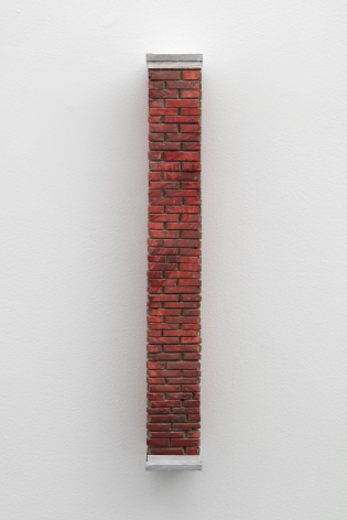 A sculpted brick column, installed on the wall.