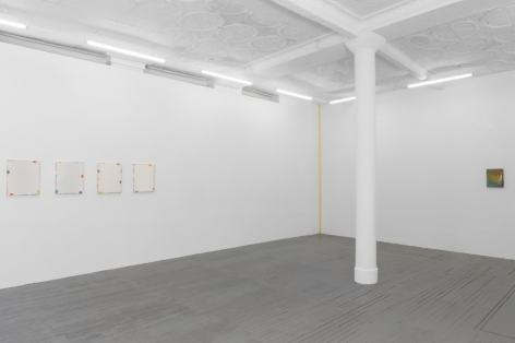A photograph of the gallery's back quadrant. At left are 4 paintings by Monick with a cream ground. There is a yellow ribbon work in the back corner, and another Monick painting on the back-right wall.