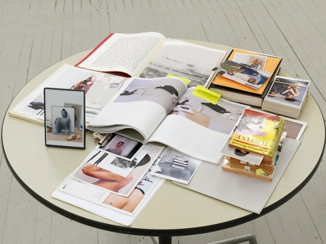 A round cream-colored table covered with the items described in the artwork's caption. They are layered upon one another, some invisible beneath piles of paper.