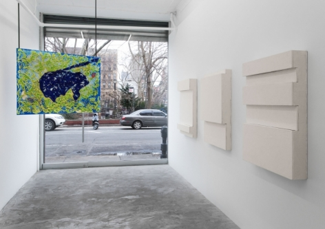A photograph of the gallery looking out, with 3 works on the right wall and one hanging painting