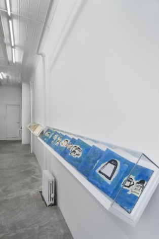 A photograph of the 124 Forsyth gallery, with 2 vitrines containing leporellos by Etel Adnan on the right wall