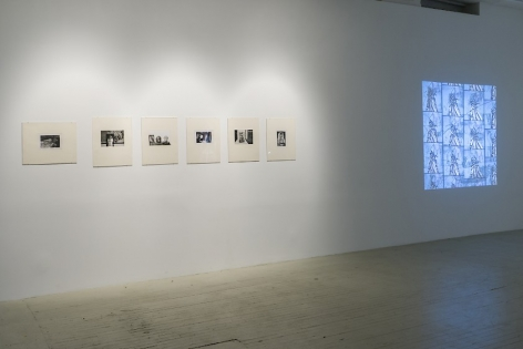 A photograph of the wall directly at left of the entrance to the gallery, which has 6 black and white photographs by Hervé Guibert in cream mattes followed by a Luther Price video projection a bit further down the wall, depicting a butterfly on a blue background.