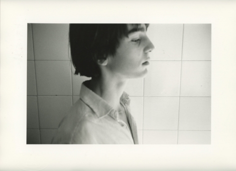 A black and white photograph of the side-profile of Vincent, a young boy in a collared shirt, against square ceramic tiles. His eyes are closed, and we see him from the shoulders up.