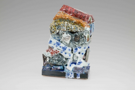 A sculpture of glazed and unglazed clay, stacked, with several different visible patters (cigarette images, blue flowers, red roses, orange fried chicken)