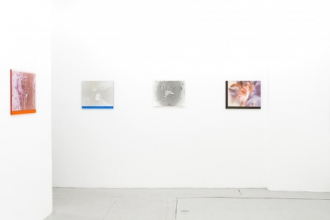 4 color photographs on plexiglass installed around the corner of the room, 1 on the left, 3 on the wall facing the viewer