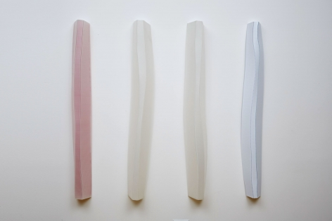 A photograph of 4 sculptures installed upon the wall. They follow the order of colors mentioned in the title (red, white, white, blue), and there is approximately 12 inches between each column.