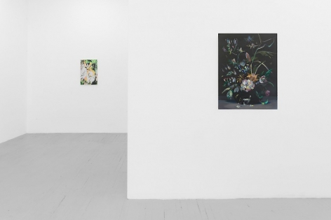 A close view photograph of a painting on black ground on the gallery's temporary wall with flowers. The back wall has an abstract painting with tones of orange, yellow, and green.