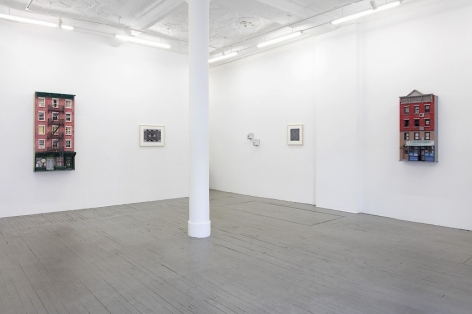 A photograph of half of the gallery. The back wall holds a sculpture of the facade of a building, followed by a black and white drawing, then 2 small sculptures on the opposite right-side wall, and a sculpture of a building facade at right.