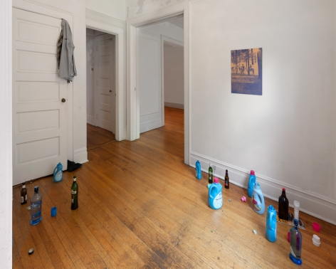 A photograph of an installation in an entry foyer, with a shirt over a door, open detergent and liquor bottles, and a work on the wall at right