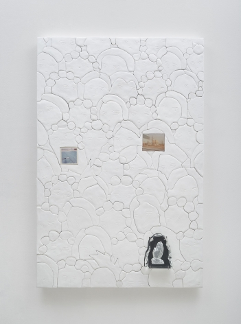A photograph of a predominantly white surface that has 3 collage elements upon it that depict artworks (2 landscapes, 1 set of praying hands). There are circles carved into the surface that appear like soap suds in cartoon-form.