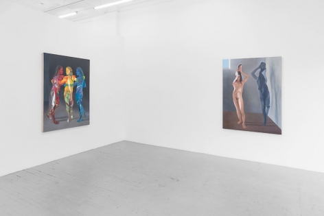 A photograph depicting two large paintings: one with three figures standing together, painted in red, yellow, and blue; the other with a single female naked body flattened like a paper doll, folding over herself, with an identical grey silhouette to the right of her.