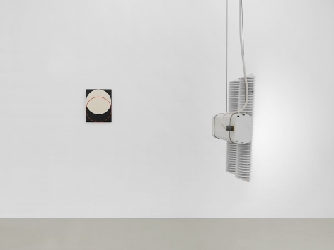 A side-view of the LED industrial light int he back gallery and an Ulrike Muller enamel on steel artwork, which depicts 2 circles overlapping. One circle is a red outline, the other is a filled beige circle.