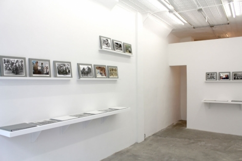 A photograph of the gallery including images on shelves leaning against the wall in gray frames
