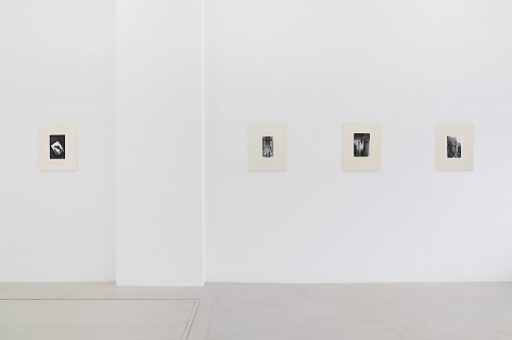 An installation view of 5 black and white Guibert photographs, placed in cream-colored frames made from watercolor paper, hung on the wall