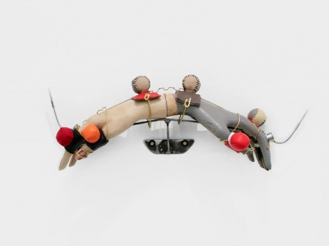 "Two mannequin hands attached at the wrists, installed on the wall like a downward ""U"". There are muffs (small foam balls covered in colored leather) and gaffs (sharp blades) attached to the hands with brass wire."