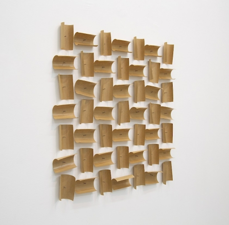 A gummed paper tape installation; 49 squares of tape are pinned at the center with a nail, and curling to create an alternating pattern