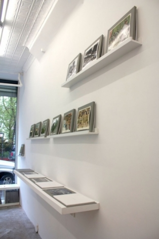 A photograph of 1 shelf and 2 platforms on the wall that host books (shelf) and photographs on view