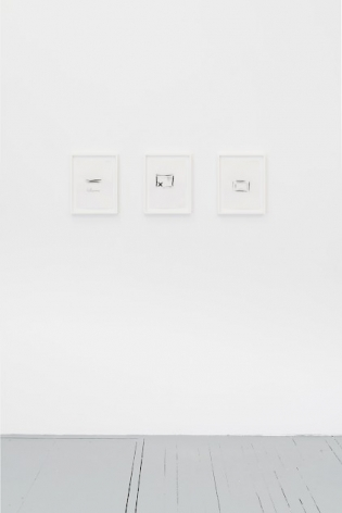 A photograph of three black and white drawings, framed in white, installed on the wall in a single row.