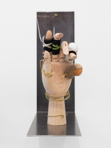 A wooden mannequin hand set upon a raw steel shelf that projects outward from the wall. There are muffs (leather-covered balls of foam) and gaffs (small blades) attached to the hand with brass wire.