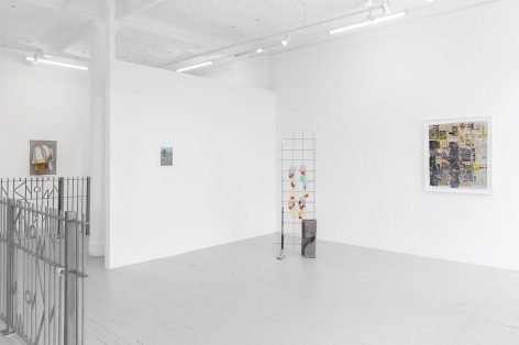 A photograph of the front quadrant of the gallery. At the left are two steel fences, excerpted, installed on the ground. There is a sculpture on the ground in the center-background of the gallery. On the temporary wall is an unframed print; on the right wall is a framed artwork made up of newspaper collages.