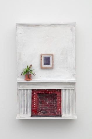 A sculpture of a white wall and a white mantle, with a brick fireplace that is red. There is a plant on the mantel, and a small drawing, also by Buffon, on the wall. The whole sculpture is installed on the wall.