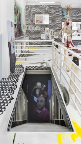 A photograph of the inside of the gallery that provides a direct view down the staircase, which has a video playing. There are white rails surrounding the staircase. In the distance in the background is the window of the gallery at right, and a wall with the site-specific installation of black and white triangles. Upon the walls in the background are flat works installed on the walls.