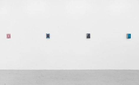 A single wall straight on with four small abstract paintings, who's detailed are indiscernible.