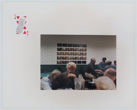 A photograph of elderly men in a card hall with a grid of photographs behind them. The photograph is presented on a mount with a 9 of Hearts playing card at top-left