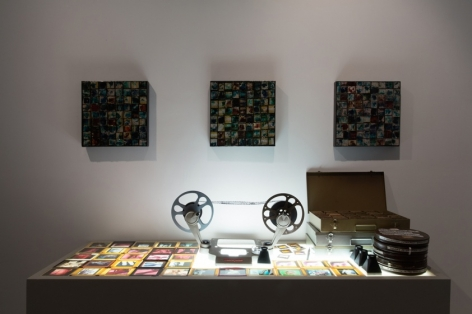 A photograph of an illuminated vitrine that includes film slides and 2 small film-reels on a reader. There are 3 metal boxes stacked on top of one another at the right of the table. Above the table are 3 tessellated square artworks with film negatives.