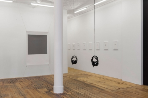 A photograph of the view of the back quadrant of the gallery. There is one screenprint with a gray center, 2 sets of headphones hanging in the center of the room, and a series of smaller works on the wall framed in white. Those works run in a row toward the back office.