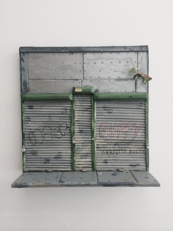 A sculpture of a facade of a building in New York City. The facade is mostly metal, and we find the sidewalk out front. The storefront is shuttered.