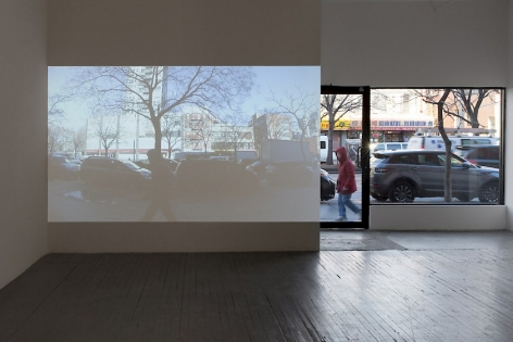 A photograph from the inside of the gallery. On a white wall is a projection of the sidewalk. To the right of the projection is the front window of the gallery, which depicts the sidewalk and street traffic on Delancey Street.