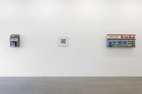 A photograph of the left side of the gallery, which is a single wall with a NY Pizza storefront sculpture followed by a framed black and white drawing, and followed by a sculpture of the facade of Rite Aid.