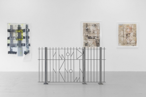 "A photograph of one wall of the gallery with 3 works upon it. In the foreground is a fence that says ""KNOWN UNKNOWN"" in it's metalwork."