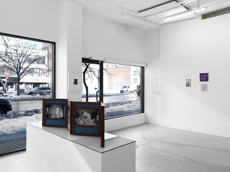 A photograph of the front quadrant of the gallery with the gallery's windows. Dayanita Singh's unfurled book-object on a pedestal is in the foreground; in the background are 2 drawings by Bracha Ettinger, and one photograph to the left of them.