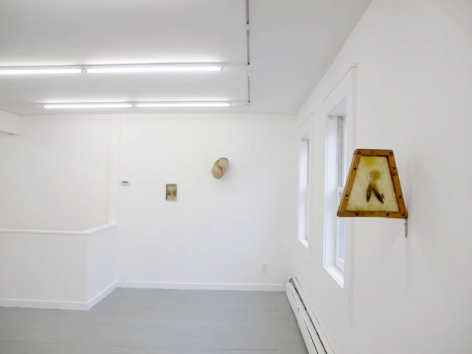 A photograph of the same 3 works on 2 walls, from a different angle