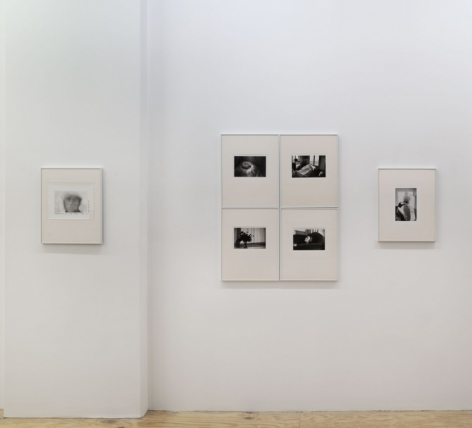 A photograph that is a tighter crop of one wall of the gallery. There is 1 photograph, then 4 photographs at the right that are arranged in a rectangle with all corners touching, followed by one more photograph. The images are installed in cream mattes with silver frames.