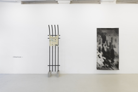 installation view showing the title of the show, the fence sculpture and a large black and white photograph that is tacked to the wall and that depicts an abstraction of draped netting commonly seen on construction sites