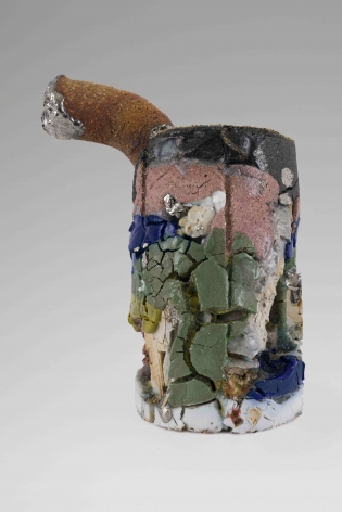 A mixed stone sculpture about the size of a beer can, with cracks throughout. Tones of moss green, pink, blue, and white are painted upon the surface. There is a small tube curving up and off the top of the form, with a silver drip at the end.