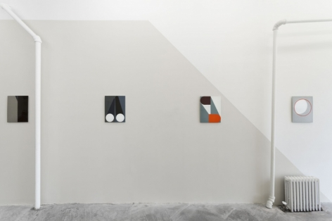 4 enamel paintings hung on a wall. the one work at right is on a white wall, with a diagonal gray cut to the left that takes over the wall.