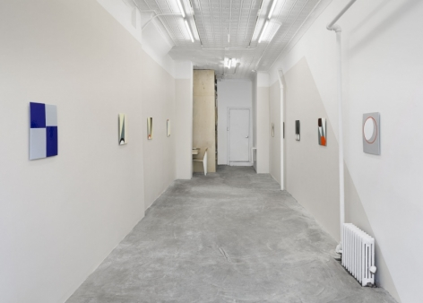 A photograph of the gallery, with enamel paintings on both walls in a single row. The left wall is grey, right wall have a gray slice.