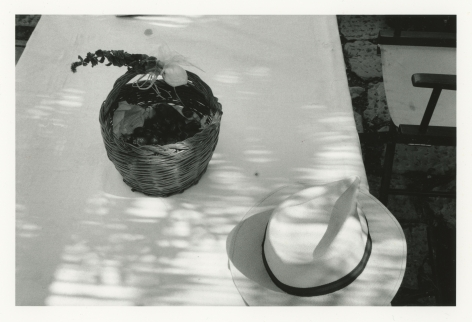 a black and white photograph of a hat and a basket on a table, shot from above