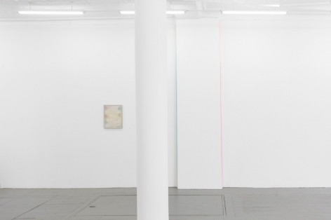 A photograph of the gallery's interior with a white pole in the foreground: to the left is a pale painting by Monick, and at right are two ribbon artworks (blue, pink)