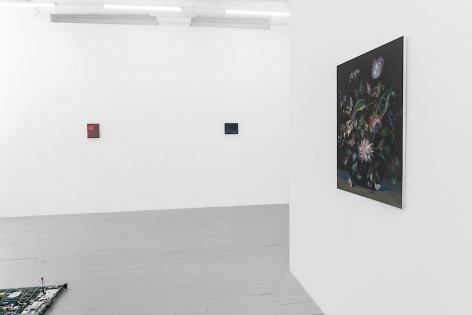 A photograph of the gallery from the side of the temporary wall. There is a floral still life at-right, and on the far wall are two small abstract paintings.